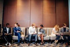 Бизнесмены ждать собеседование для приема на работу, говоря Стоковая Фотография