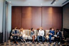 Бизнесмены ждать собеседование для приема на работу, говоря Стоковое фото RF
