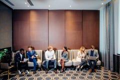 Бизнесмены ждать собеседование для приема на работу, говоря Стоковые Фотографии RF