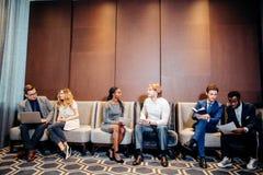 Бизнесмены ждать собеседование для приема на работу, говоря Стоковые Фото