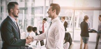 бизнесмены закрывают офис рук трястия вверх Стоковое фото RF