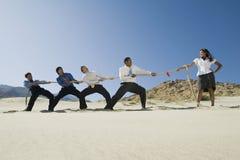 Бизнесмены играя перетягивание каната против одной женщины Стоковое Изображение RF