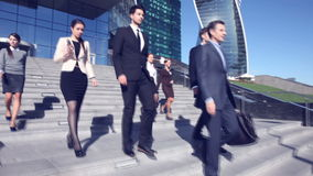 Бизнесмены идут вниз с лестниц