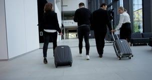 Бизнесмены идя с, который катят сумками акции видеоматериалы