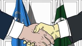 Бизнесмены или политики трясут руки против флагов Организации Объединенных Наций и Пакистана E бесплатная иллюстрация