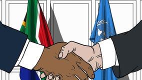 Бизнесмены или политики трясут руки против флагов Южной Африки и Организации Объединенных Наций Официальное заседание или сотрудн бесплатная иллюстрация