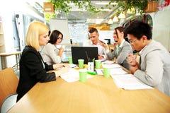 Бизнесмены имея встречу вокруг таблицы Стоковое Фото