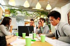 Бизнесмены имея встречу вокруг таблицы Стоковая Фотография