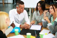 Бизнесмены имея встречу вокруг таблицы Стоковые Изображения RF