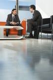 Бизнесмены имея встречу в лобби Стоковые Фотографии RF