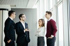 Бизнесмены имея неофициальное заседание в современном офисе на предпосылке окон Стоковые Изображения RF