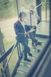 Бизнесмены имея переговор на лестницах строения дела стоковые фотографии rf