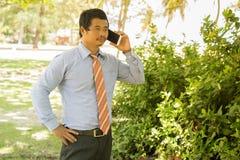 Бизнесмены используют smartphones для того чтобы побеседовать с клиентами Стоковая Фотография
