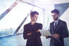 Бизнесмены используя компьтер-книжку в офисе Стоковые Фото