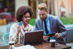 Бизнесмены используя компьтер-книжку и кредитную карточку внешние Стоковые Фото
