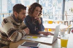 Бизнесмены используя компьтер-книжку на таблице в кафе Стоковые Фотографии RF