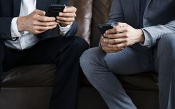 Бизнесмены используя мобильные телефоны сидя на кресле Стоковые Фото
