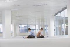 Бизнесмены используя компьтер-книжки в пустых размерах офиса Стоковое Изображение RF