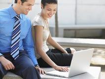 Бизнесмены используя компьтер-книжку вне офиса Стоковые Фото