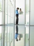 Бизнесмены используя компьтер-книжку в встрече Стоковые Изображения