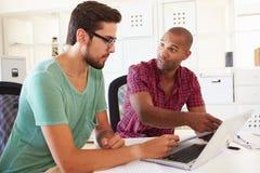 Бизнесмены используя компьтер-книжку в офисе начинают вверх дело Стоковое Фото