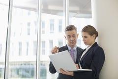 Бизнесмены используя компьтер-книжку в офисе Стоковое Изображение