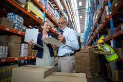 Бизнесмены используя компьтер-книжку и сочинительство на бумаге Стоковое Изображение RF