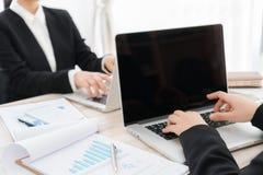 Бизнесмены используя компьтер-книжку и финансовые диаграммы на встрече Стоковое Фото