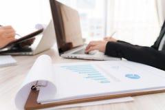 Бизнесмены используя компьтер-книжку и финансовые диаграммы на встречать o Стоковое Фото