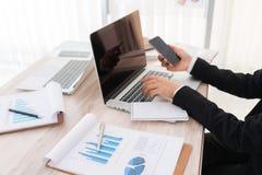 Бизнесмены используя компьтер-книжку и финансовые диаграммы на встрече Стоковые Фотографии RF