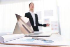 Бизнесмены используя компьтер-книжку и финансовые диаграммы на встрече Стоковые Фото