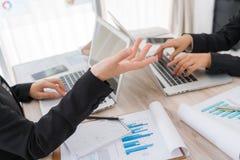 Бизнесмены используя компьтер-книжку и финансовые диаграммы на встрече Стоковое Изображение