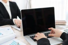 Бизнесмены используя компьтер-книжку и финансовые диаграммы на встрече Стоковые Изображения