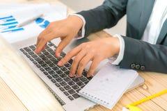 Бизнесмены используя компьтер-книжку и финансовые диаграммы на встречать  Стоковая Фотография
