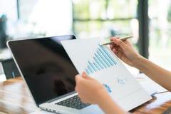 Бизнесмены используя компьтер-книжку и финансовые диаграммы на встречать  Стоковое Изображение RF