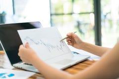 Бизнесмены используя компьтер-книжку и финансовые диаграммы на встречать  Стоковые Изображения RF