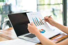 Бизнесмены используя компьтер-книжку и финансовые диаграммы на встречать  Стоковая Фотография RF