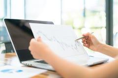 Бизнесмены используя компьтер-книжку и финансовые диаграммы на встречать  Стоковое Изображение