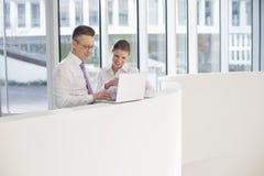 Бизнесмены используя компьтер-книжку на перилах в офисе Стоковая Фотография