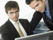 Бизнесмены используя компьютер в офисе Стоковые Фото