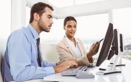 Бизнесмены используя компьютер в офисе Стоковые Фотографии RF