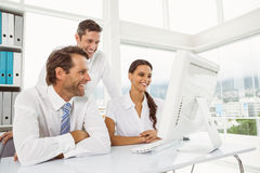 Бизнесмены используя компьютер в офисе Стоковые Изображения RF