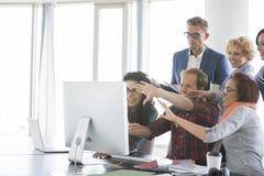 Бизнесмены используя компьютер в офисе Стоковые Изображения