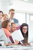 Бизнесмены используя компьютер в творческом офисе Стоковая Фотография