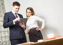 2 бизнесмены используя планшет в офисе Стоковые Фотографии RF