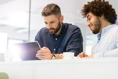 Бизнесмены используя планшет в офисе Стоковые Фотографии RF