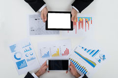 Бизнесмены используя таблетки цифров с финансовыми диаграммами на таблице Стоковое Изображение