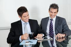 Бизнесмены используя таблетку цифров в офисе Стоковые Фото
