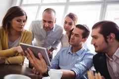 Бизнесмены используя таблетку цифров в офисе Стоковое Изображение RF