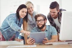 Бизнесмены используя цифровую таблетку пока сидящ на столе компьютера Стоковая Фотография